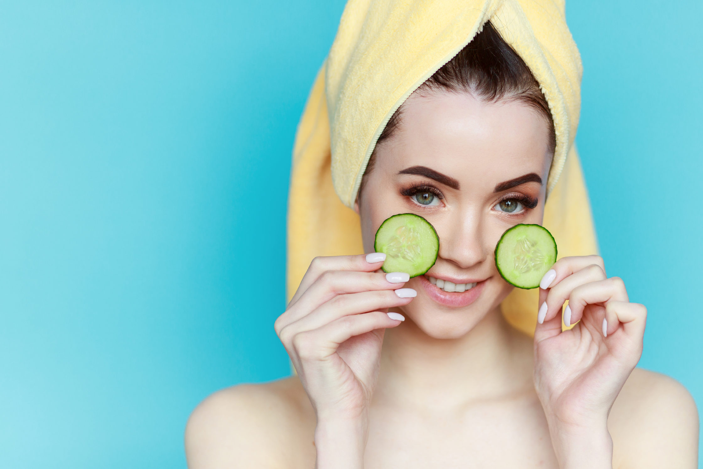 portrait-young-beautiful-woman-with-healthy-skin-holds-two-piece-cucumber-near-face