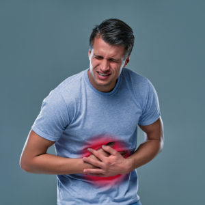 A man touching his stomach, on gray background with copy space. Stomach pain and others stomach disease concept.